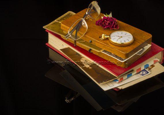 Fotografie pe fundal negru cu carte, scrisori si fotografii vechi, ceas si ochelari