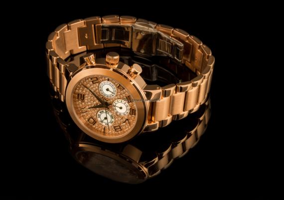 Fotografie ceas auriu pe fundal negru cu reflexie naturala