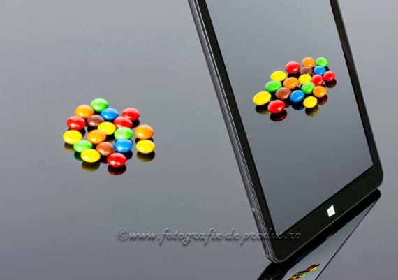 Fotografie de produs compozitie pe fundal negru cu reflexie, tableta fotografiind bomboane colorate