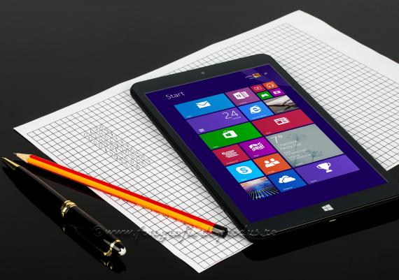 Fotografie compozitie pe fundal negru cu tableta pe foaie de calcul, stilou si creion